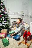 Nettes Mädchen, das nahe dem Weihnachtsbaum in einem Reinraum sitzt Neues Y Lizenzfreies Stockbild