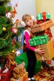 Nettes Mädchen, das nahe dem Weihnachtsbaum und den Griffen eine Vielzahl von Kästen mit Geschenken steht Lizenzfreie Stockfotos