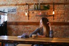 Nettes Mädchen, das nahe Tabelle mit Schale Cappuccino und Notizbuch im gemütlichen Luncheonette sitzt Stockbild