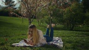 Nettes Mädchen, das online am intelligenten Telefon im Park plaudert stock video
