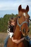 Nettes Mädchen, das Pferd umarmt stockbild