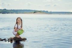 Nettes Mädchen, das sich vorbereitet, Papierboot am See zu starten Stockfoto