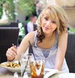 Nettes Mädchen, das Teigwaren am im Freienkaffee isst Lizenzfreie Stockfotos