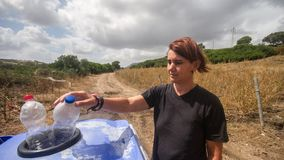 Nettes Mädchen, das zwei Plastikflaschen in den überschüssigen Behälter in der Zeitspanneansicht wirft stock footage