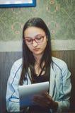 Nettes Mädchen in den Gläsern, die einen Notizblock in ihren Händen halten stockbilder