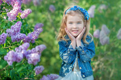 Nettes Mädchen in den Matrosen mit dem feenhaften luftigen Rock, der nah an Fliederbusch steht stockbilder