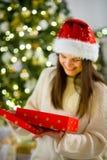 Nettes Mädchen der Brunette, der einen Kasten mit dem Weihnachtsgeschenk öffnet Lizenzfreies Stockfoto