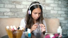 Nettes Mädchen in der hörenden Musik der Kopfhörer und der Hauptkleidung, die Manikürepoliernägel mit Datei macht stock footage