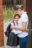 Nettes Mädchen in der Schuluniform mit dem Rucksack, der ihre Mutter umarmt Stockfotografie
