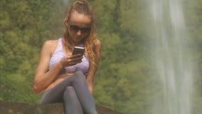 Nettes Mädchen in der Sonnenbrille liest sms nahe Wasserfall stock video footage