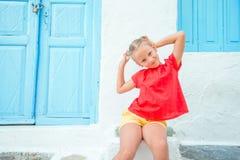 Nettes Mädchen an der Straße des typischen griechischen traditionellen Dorfs auf Mykonos-Insel, in Griechenland lizenzfreie stockbilder