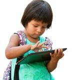 Nettes Mädchen des amerikanischen Ureinwohners, das auf Tablette schreibt. Stockfotografie