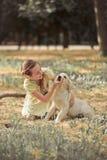 Nettes Mädchen des jungen jugendlich der reizenden Szene des Retrieverwelpen, das Sommerzeitferien mit Labrador-Welpen des Elfenb stockfoto