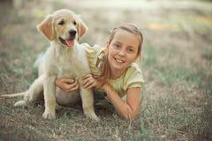 Nettes Mädchen des jungen jugendlich der reizenden Szene des Retrieverwelpen, das Sommerzeitferien mit Labrador-Welpen des Elfenb lizenzfreies stockfoto