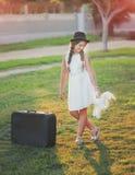 Nettes Mädchen in einem Hut und mit einem Koffer Stockbilder