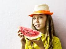 Nettes Mädchen in einem Strohhut mit einer reifen Wassermelone Lizenzfreies Stockfoto