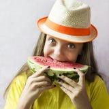 Nettes Mädchen in einem Strohhut mit einer reifen Wassermelone Stockfotografie