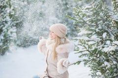 Nettes Mädchen in einer beige Jacke sitzt und wirft oben einen Schnee nahe Fichten an einem Wintertag lizenzfreie stockbilder