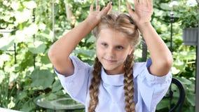 Nettes Mädchen in einer Freiterrasse, die den Spaß zeigt Ohren mit den Händen hat Glückliche Kindheit Lachen Genießen des sonnige stock video footage