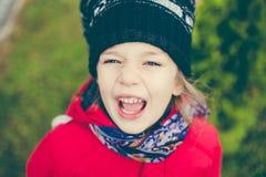 Nettes Mädchen in einer Jacke und in einem Hut auf dem stree Lizenzfreies Stockfoto