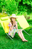 Nettes Mädchen entspannt sich mit Saft am Stuhl auf Gras Stockfoto