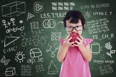 Nettes Mädchen essen Apfel in der Klasse lizenzfreies stockbild