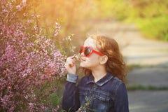 Nettes Mädchen genießt den Geruch der blühenden Mandelblume Gesund, lizenzfreies stockbild