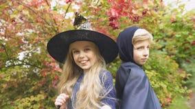 Nettes Mädchen im Hexenhut und -jungen im Umhang, der für Kamera im Wald, Halloween aufwirft stock footage