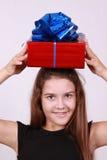 Nettes Mädchen im schwarzen Kleid hält Geschenk auf Kopf Stockbilder