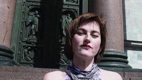 Nettes Mädchen im Sommerkleid lächelnd vor alter orthodoxal Kirchentür stock video footage