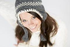 Nettes Mädchen im Winter kleidet oben schauen mit dem reizenden Lächeln. Lizenzfreie Stockfotografie