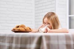 Nettes Mädchen ist Trinkmilch nahe Platte mit Plätzchen Stockfotografie