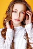 Nettes Mädchen Jugend mit dem langen gelockten Haar, das Studionaturporträt aufwirft Stockfotografie