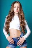 Nettes Mädchen Jugend mit dem langen gelockten Haar, das Studionaturporträt aufwirft Lizenzfreie Stockfotos