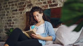 Nettes Mädchen liest lustiges Buch im Schlafzimmer, das auf bequemem Bett liegt, Schale mit Getränk lächelt und hält Hobby, glück stock video footage