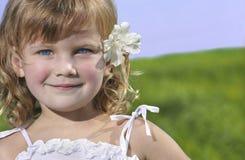 Nettes Mädchen mit Blume auf blauem Himmel und grünem Gras Stockfotografie