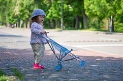 Nettes Mädchen mit dem Wagen im Park Lizenzfreies Stockfoto