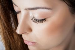Nettes Mädchen mit den ausgedehnten silk Wimpern und den Augen oben geschlossen in einem Schönheitsstudio, Abschluss stockfoto