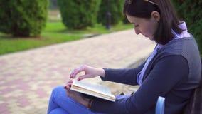 Nettes Mädchen mit einem Buch auf einer Bank stock video footage