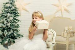 Nettes Mädchen mit Geschenken auf dem Hintergrund eines Weihnachtsbaums in einem Reinraum lizenzfreie stockfotos