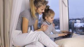 Nettes Mädchen mit ihrer Mutter, die Laptop-Computer verwendet stock footage