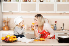 Nettes Mädchen mit ihrer Mutter, die Orange während isst Lizenzfreie Stockbilder