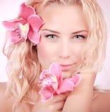 Nettes Mädchen mit Orchideenblumen Lizenzfreie Stockbilder