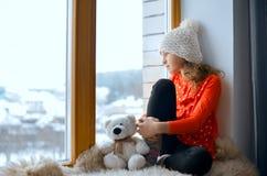 Nettes Mädchen mit sitzendem allein nahem Fenster des langen Haares auf einem Fensterbrett Lizenzfreies Stockbild