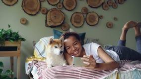 Nettes Mädchen nimmt selfie mit dem Haustier, das mit dem schönen Hund aufwirft, der auf dem Bett liegt, das Spaß und das Lachen  stock video footage