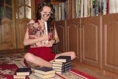 Nettes Mädchen sitzt im Lotussitz und hält ein schweres Buch mit zwei Händen in der Bibliothek Stockfotos