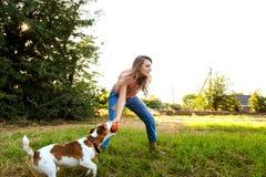 Nettes Mädchen spielt mit ihrem Hund im Park Stockfotografie