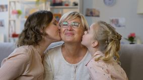 Nettes Mädchen und ihre Mutter, welche die Oma, Familie herzlich zusammen umfasst, glücklich küsst stock footage