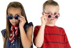 Nettes Mädchen und Junge, die über amerikanischen patriotischen Gläsern blickt Stockfotos