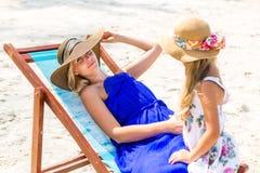 Nettes Mädchen und schöne Mutter auf dem Strand Stockbilder